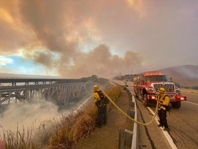 In this photo provided by the Santa Barbara County Fire Department, firefighters extinguish flames Tuesday afternoon, Oct. 12, 2021, that have spotted ahead of the fire front along Highway 101 southbound at Vista Point, north of Refugio State Beach in Santa Barbara County, Calif. (Mike Eliason/Santa Barbara County Fire Department via AP)