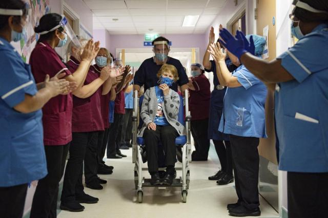 FILE - In this Tuesday Dec. 8, 2020 file photo Margaret Keenan, 90, is applauded by staff as she returns to her ward after becoming the first patient in the United Kingdom to receive the Pfizer-BioNTech COVID-19 vaccine, at University Hospital, Coventry, England. (Jacob King/Pool via AP, File)