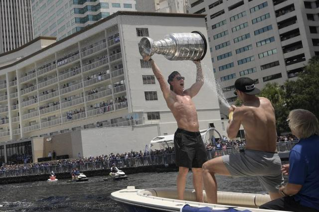 Tampa Bay Lightning left wing Ondrej Palat is sprayed by defenseman Jan Rutta, while hoisting the Stanley Cup during the NHL hockey Stanley Cup champions' Boat Parade, Monday, July 12, 2021, in Tampa, Fla. (AP Photo/Phelan M. Ebenhack)