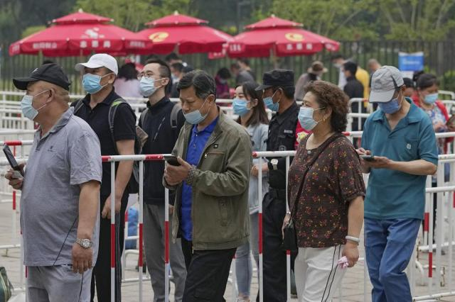 Residents wearing face masks to help curb the spread of the coronavirus line up to receive the Sinopharm COVID-19 vaccine at the Central Business District in Beijing, Wednesday, June 2, 2021. (AP Photo/Andy Wong)