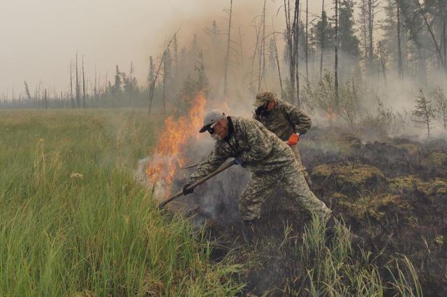 Volunteers douse a forest fire in the republic of Sakha also known as Yakutia, Russia Far East, Saturday, July 17, 2021. Russia has been plagued by widespread forest fires, blamed on unusually high temperatures and the neglect of fire safety rules, with the Sakha-Yakutia region in northeastern Siberia being the worst affected. (AP Photo/Ivan Nikiforov)