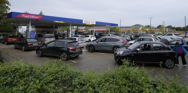 Drivers queue for fuel at a petrol station in London, Thursday, Sept. 30, 2021. Many gas stations around Britain have shut down in the past five days after running out of fuel, a situation exacerbated by panic buying among some motorists. Long lines of vehicles formed at pumps that were still open, blocking roads and causing traffic chaos. Some drivers have had to endure hourslong waits to fill up. (AP Photo/Frank Augstein)