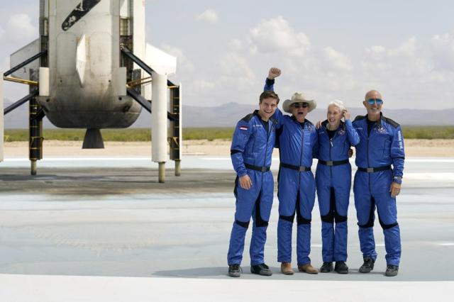 Oliver Daemen, from left, Jeff Bezos, founder of Amazon and space tourism company Blue Origin, Wally Funk and Bezos' brother Mark pose for photos in front of the Blue Origin New Shepard rocket, left rear, after their launch from the spaceport near Van Horn, Texas, Tuesday, July 20, 2021. (AP Photo/Tony Gutierrez)