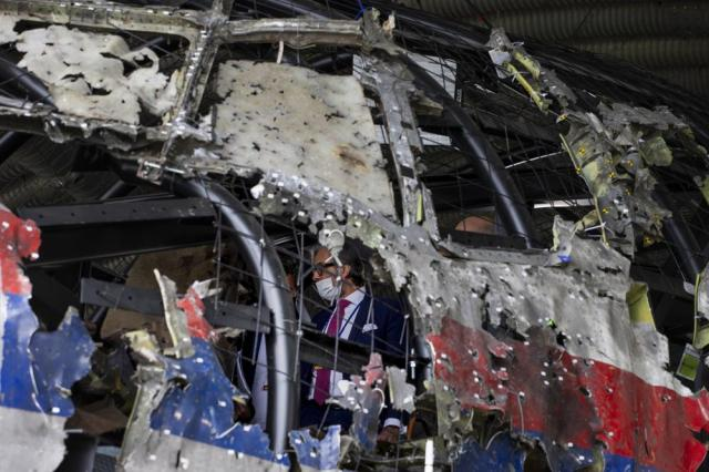 Trial judges and lawyers are seen inside as they view the reconstructed wreckage of Malaysia Airlines Flight MH17, at the Gilze-Rijen military airbase, southern Netherlands, Wednesday, May 26, 2021. (AP Photo/Peter Dejong, Pool)