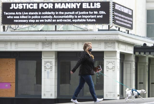Monica Colby walks her dog, Piper, past the marquee on the historic Pantages Theater that honors Manny Ellis in downtown Tacoma, Washington, on Thursday, May 27, 2021. Earlier in the day, the state's attorney general announced criminal charges against three Tacoma police officers involved in Ellis' death. (Tony Overman/The News Tribune via AP)