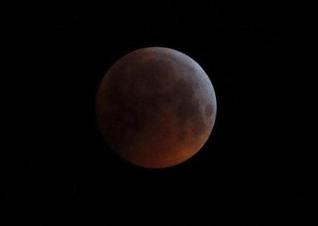 """FILE - In this Monday, Jan. 21, 2019 file photo, the Earth's shadow falls across the full moon seen above Brighton, southeast England. The first total lunar eclipse in more than two years coincides with a supermoon this week for a cosmic show. This super """"blood"""" moon will be visible Wednesday, May 26, 2021 across the Pacific _ offering the best viewing _ as well as the western half of North America, bottom of South America and eastern Asia. (AP Photo/Alastair Grant, File)"""