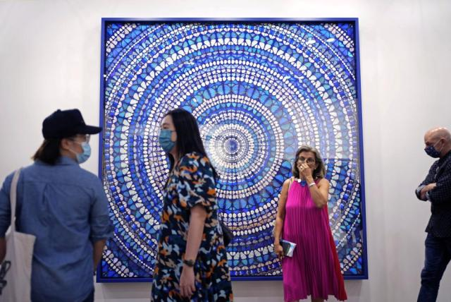 """Visitors pass an artwork titled """"Martyr, 2019"""" created by British artist Damien Hirst at Art Basel in Hong Kong Wednesday, May 19, 2021. Art Basel, one of the world's most prestigious modern and contemporary art exhibitions, is returning to Hong Kong in its ninth edition. The prestige art fair is hosting 104 galleries from 23 countries and territories. (AP Photo/Vincent Yu)"""