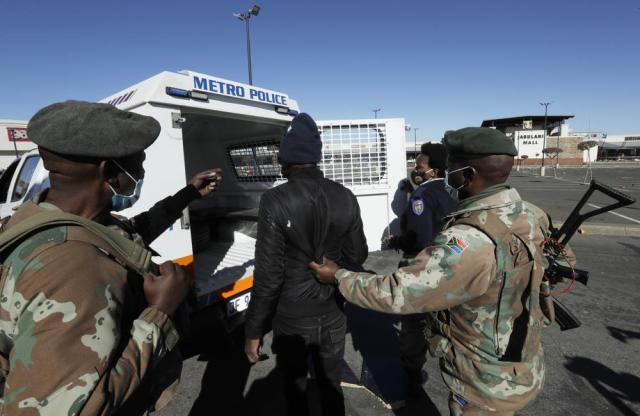 A man suspected of looting is arrested at a shopping mall in Soweto, near Johannesburg, Tuesday July 13, 2021. South Africa's rioting continued Tuesday as police and the military tried to halt the unrest in poor areas of two provinces, in Gauteng and KwaZulu-Natal, that began last week after the imprisonment of former President Jacob Zuma. (AP Photo/Themba Hadebe)