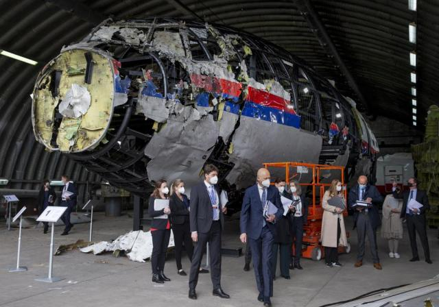 Presiding judge Hendrik Steenhuis, center, other trial judges and lawyers view the reconstructed wreckage of Malaysia Airlines Flight MH17, at the Gilze-Rijen military Airbase, southern Netherlands, Wednesday, May 26, 2021. (AP Photo/Peter Dejong, Pool)