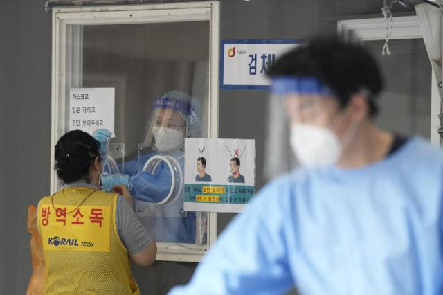 """A medical worker in a booth takes a nasal sample from a disinfection worker during coronavirus testing at a makeshift testing site in Seoul, South Korea, Sunday, Sept. 19, 2021. The letters on a jacket read, """"Disinfection."""" (AP Photo/Ahn Young-joon)"""