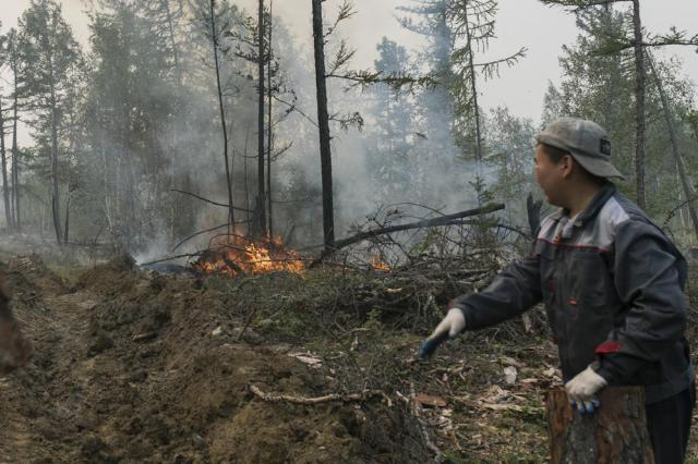 An employee of the Yakutlesresurs extinguishes a forest fire outside Magaras village 87 km. (61 miles) west of Yakustk, the capital of the republic of Sakha also known as Yakutia, Russia Far East, Sunday, July 18, 2021. Russia has been plagued by widespread forest fires, blamed on unusually high temperatures and the neglect of fire safety rules, with the Sakha-Yakutia region in northeastern Siberia being the worst affected. (AP Photo/Alexey Vasilyev)