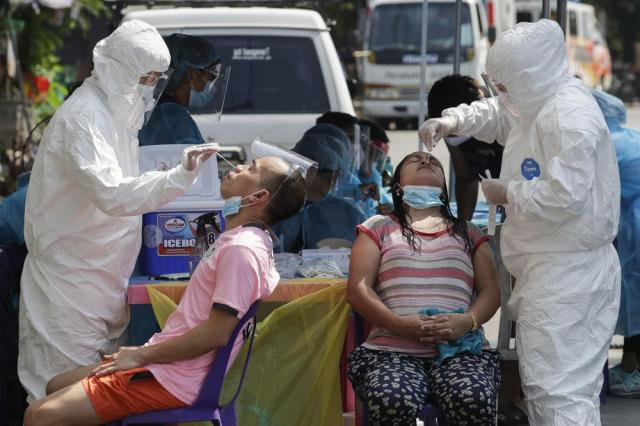 Health workers conduct a COVID-19 swab test on residents as they monitor cases at a village in Quezon City, Philippines on Monday, May 31, 2021. The president of the Philippines recently warned he will jail village leaders and police officers who don't enforce pandemic lockdown restrictions to prevent the spread of the coronavirus. (AP Photo/Aaron Favila)