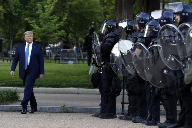 FILE - In this June 1, 2020 file photo, President Donald Trump walks past police in Lafayette Park after he visited outside St. John's Church across from the White House in Washington. An internal investigation has determined that the decision to clear racial justice protestors from an area in front of the White House last summer was not influenced by then-President Donald Trump's plans for a photo opportunity at that spot. The report released Wednesday by the Department of Interior's Inspector General concludes that the protestors were cleared by U.S. Park Police on June 1 of last year so new fencing could be installed.  (AP Photo/Patrick Semansky)