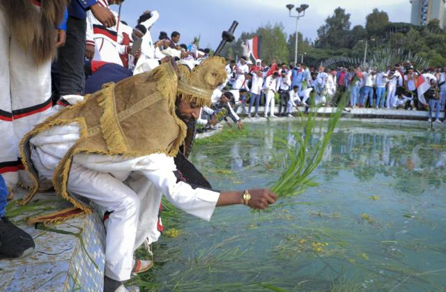 Oromos throw grass and flowers into a pool of water as they celebrate the annual Irreecha festival in the capital Addis Ababa, Ethiopia, Saturday, Oct. 2, 2021. Ethiopia's largest ethnic group, the Oromo, on Saturday celebrated the annual Thanksgiving festival of Irreecha, marking the end of winter where people thank God for the blessings of the past year and wish prosperity for the coming year. (AP Photo)