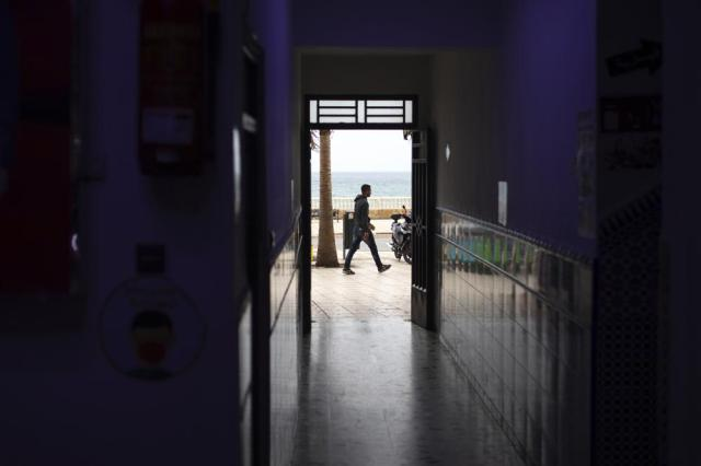A man walks past a mostly empty central market in the northern border town of Fnideq, Morocco, Thursday, May 20, 2021. An extraordinary surge of migrants seeking to leave Morocco for Spain this week has left Fnideq suffering under the strain. (AP Photo/Mosa'ab Elshamy)