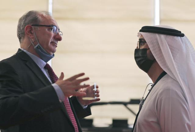 Israel's ambassador to the UAE, Eitan Na'eh, left, talks with an Emirati official during the Global Investment Forum in Dubai, United Arab Emirates, Wednesday, June 2, 2021. At the luxurious Armani hotel inside the world's tallest skyscraper in Dubai, Israelis in kippas and Emiratis in long white robes and kanduras gathered Wednesday to discuss investment opportunities aimed at making the most of deepening ties nine months after the two countries agreed to formalize relations. (AP Photo/Kamran Jebreili)