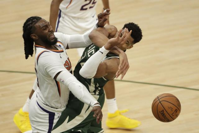 Milwaukee Bucks' Giannis Antetokounmpo, right, is fouled by Phoenix Suns' Jae Crowder, left, during the second half of Game 3 of basketball's NBA Finals, Sunday, July 11, 2021, in Milwaukee. (AP Photo/Aaron Gash)