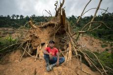 Élmer Ramírez, de 22 años, se sienta para un retrato en el lugar donde estuvo su casa antes de ser destruída por un deslave provocado por el paso de los huracanes Eta e Iota en la comunidad de La Reina, Honduras, el miércoles 23 de junio de 2021. (AP Foto/Rodrigo Abd)