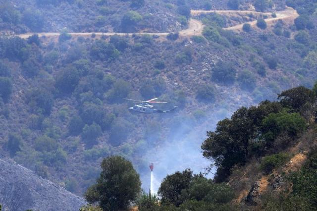 """An helicopter drops water over the mountain of Troodos in Agious Vavatsinias village, southwestern Cyprus, Sunday, July 4, 2021. Cyprus search crews discovered the bodies of four people outside a fire-swept mountain village on Sunday in what a government minister called the """"most destructive"""" blaze in the east Mediterranean island nation's history. (AP Photo/Petros Karadjias)"""