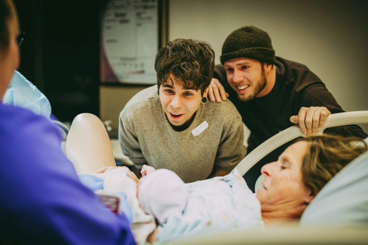 In this March 25, 2019 photo, Matthew Eledge, right, and his husband Elliot Dougherty, center, react to the birth of their daughter Uma, with Eledge's mother, Cecile Eledge, delivering the baby at the Nebraska Medical Center in Omaha, Neb. Cecile Eledge volunteered to be the surrogate mother to her grandchild, conceived with sperm from Matthew Eledge and an egg from Dougherty sister. (Ariel Panowicz via AP)