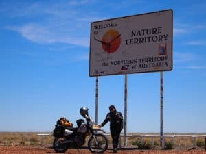 Danielle Murdoch on the first leg of her epic Australia, Africa, Europe and back trip. She is standing in front of the Northern Territory border sign. The sun is shining, it is hot and she is in full motorcycle gear. © Danielle Murdoch http://motomonkeyadventures.com/