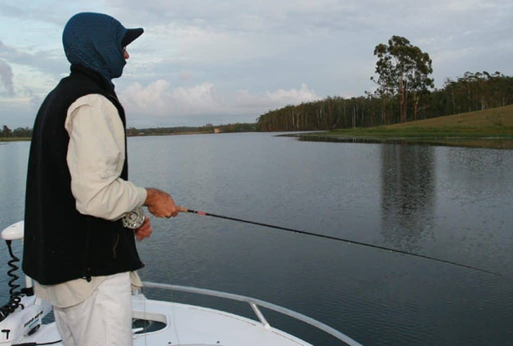 A landscape photo of a person fly fishing on a lake. The person is standing on a boat wearing a Visor Buff® as full Balaclava. The day looks cool to cold. Full cloud cover and the person is wearing a fleece west. Source: Testimonial Copyright: Permission to use on our website