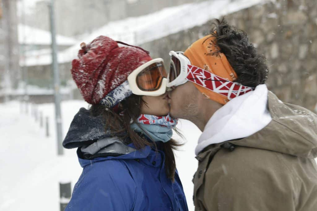 A landscape shot of a couple kissing. It is obvious that they are on ski holidays. She is wearing a Polar Buff® as scarf and a Neckwarmer Buff® as hat. He is wearing a Original Buff® as ear warmer. Source: buff.eu. Distributed for the promotion of Buff® products