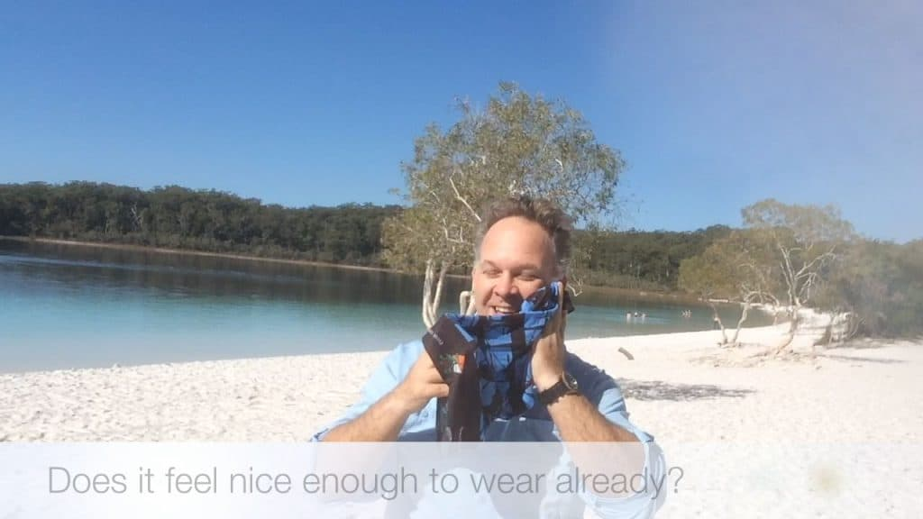 Edward holding the Original Buff® to his left cheek. He is smiling as he is enjoying a mild cooling effect.