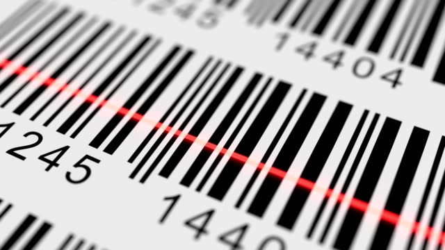 Close-up view on red laser scanning label with barcode on product.