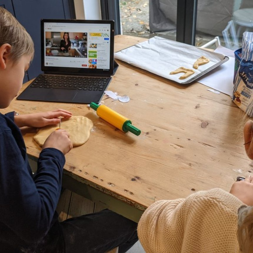 Two children roll out dough while watching an instructional video on YouTube