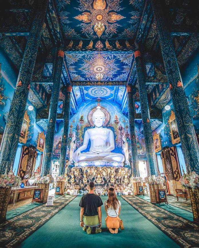 A couple praying in the main hall of a temple during their travel to Thailand