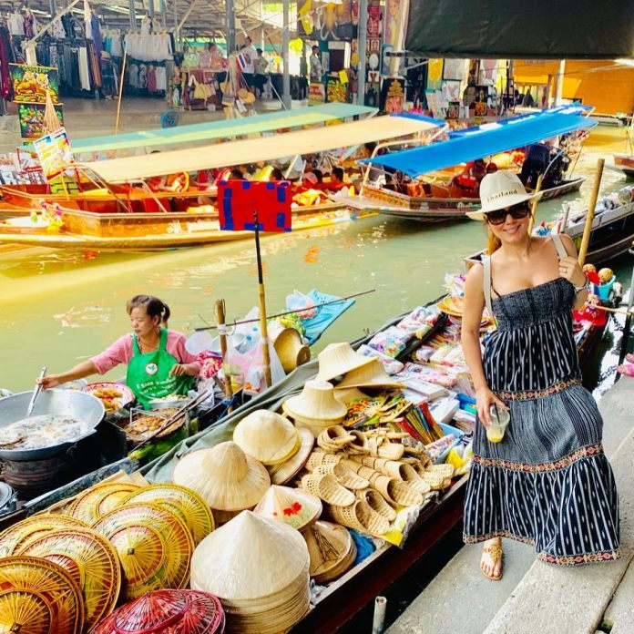 A female tourist posing near a souvenir boat in a floating market