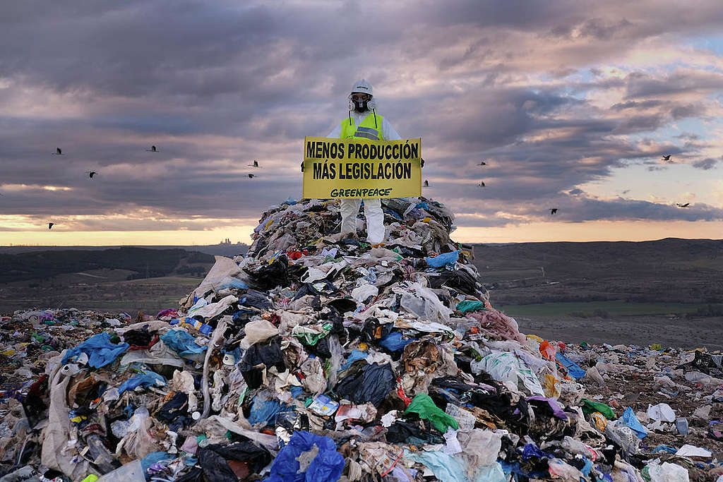 Manifestante sobre una pila de desechos plásticos