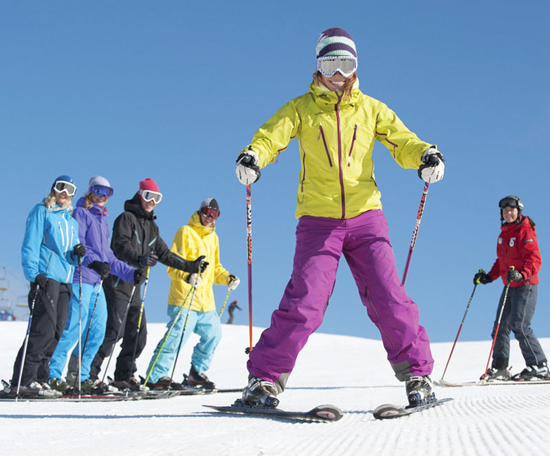 Smiling woman learns to ski in ski school GROUP LESSON