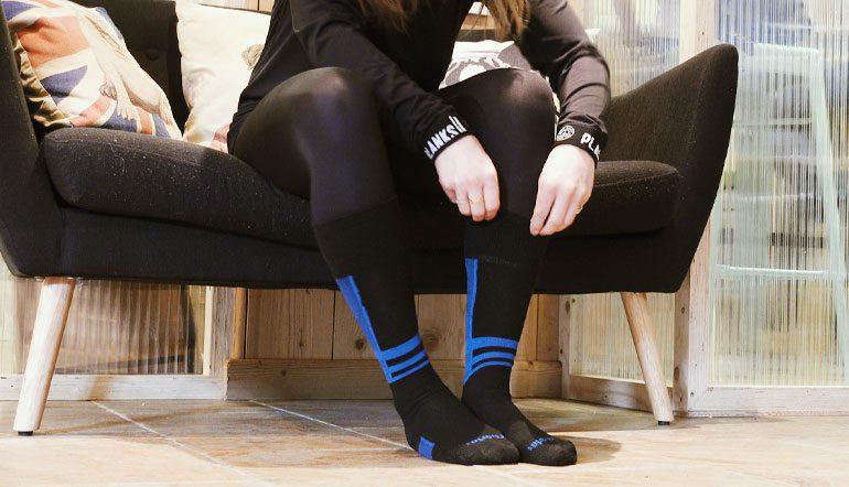woman dressing for skiing - putting on ski socks