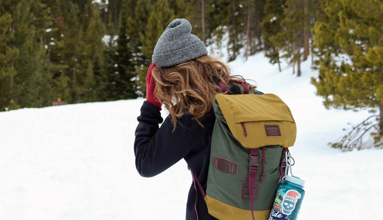 woman in snowy forest wearing beanie