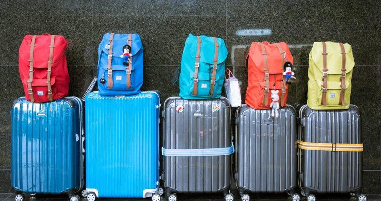five suitcases and backpacks packed for family ski trip