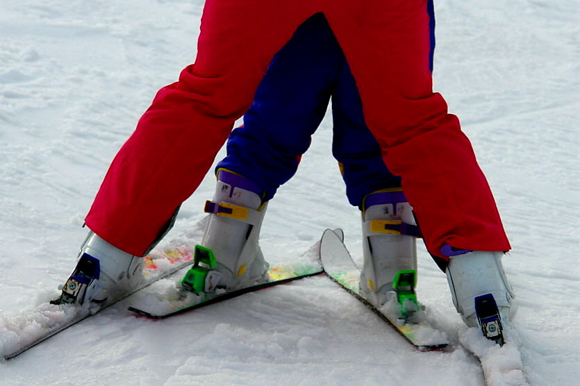 close up on legs of ski instructor and child student doing the snowplough
