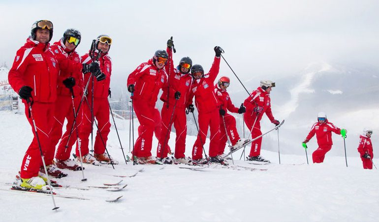 large group of happy ski school instructors in red uniforms
