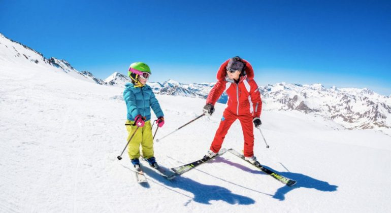 private ski instructor in red ski suit gives tips to child in kids private ski lesson
