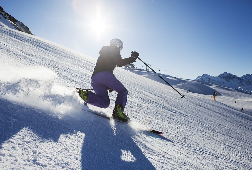 backlit shot of man telemark skiing in the sun