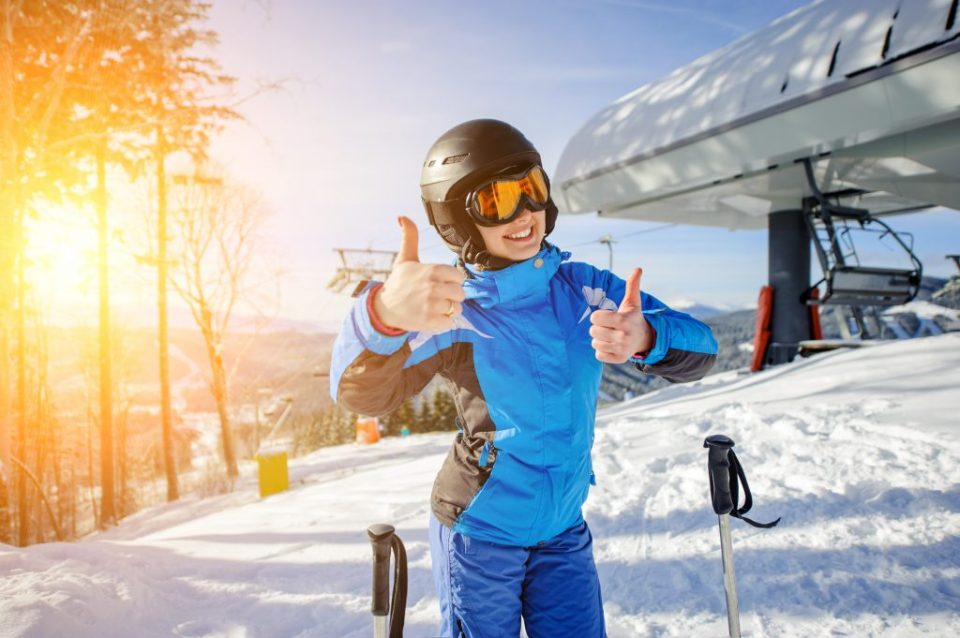 Portrait of young beautiful female skier at ski resort smiling and showing thumbs up. Winter sports concept. Woman is wearing blue jacket and blue pants, helmet and orange goggles.