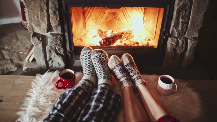 man and woman heat feet by fireplace
