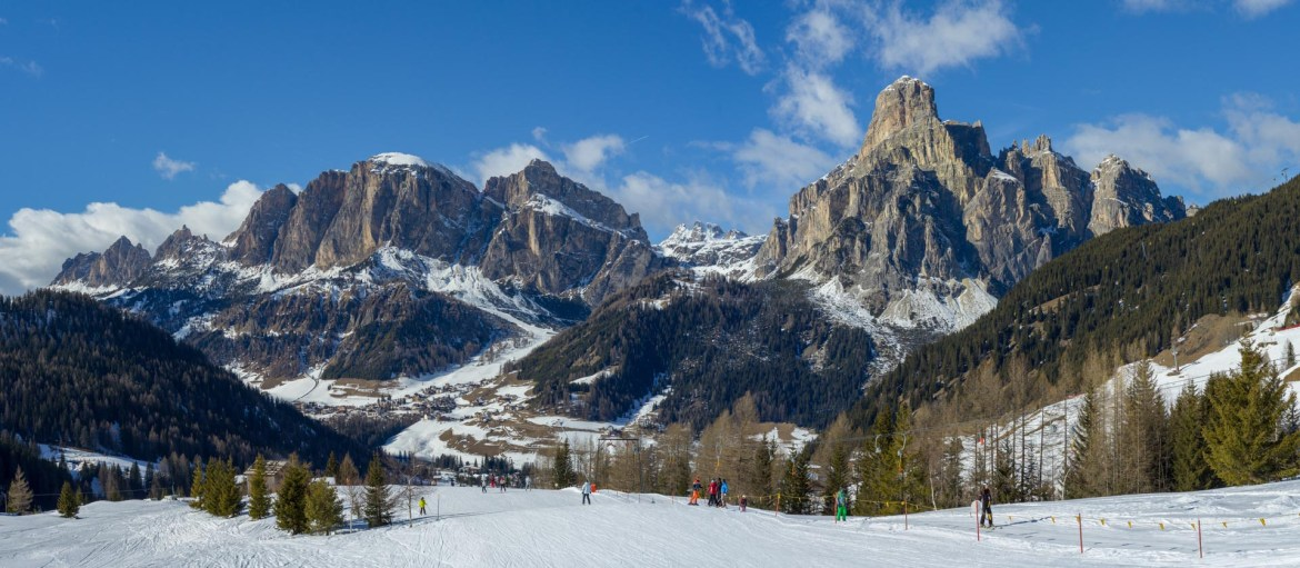 Beginner skiers enjoy a gentle piste in the aki area of Corvara as majestic peaks rise up in the distance