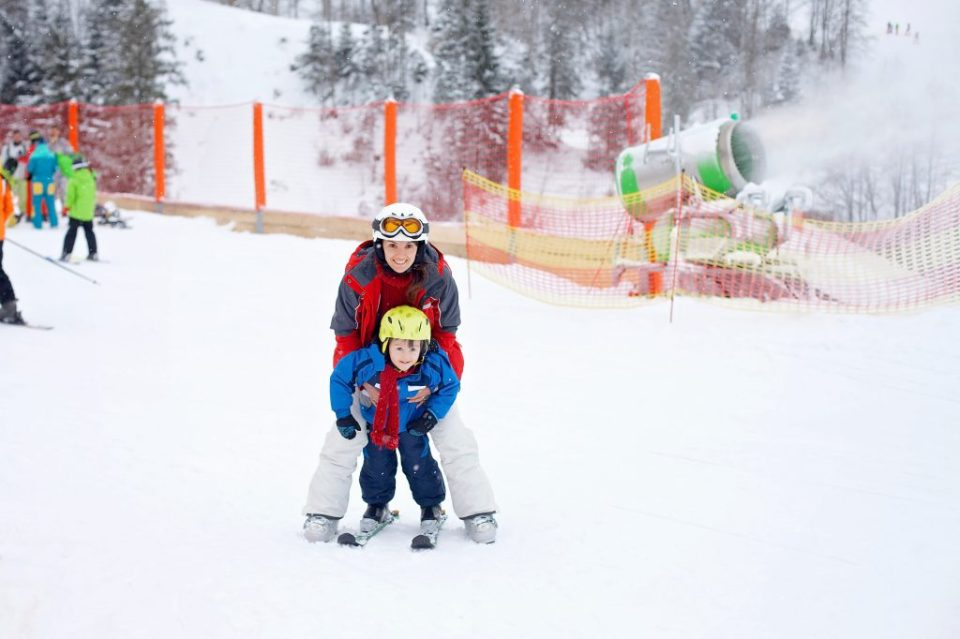 Beautiful young mom and her toddler boy, skiing in the mountains, winter time