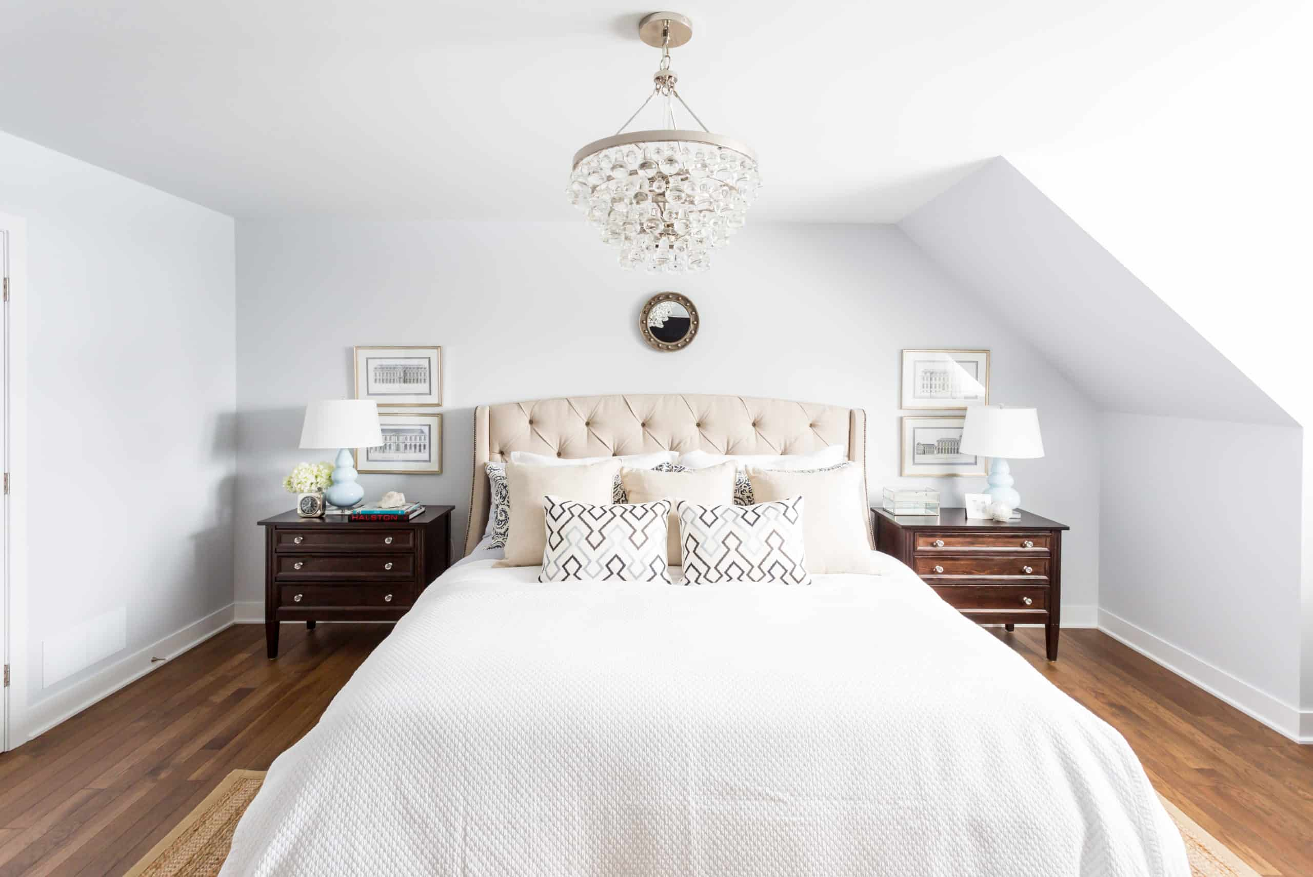 Bright white master bedroom with a chandelier above the bed