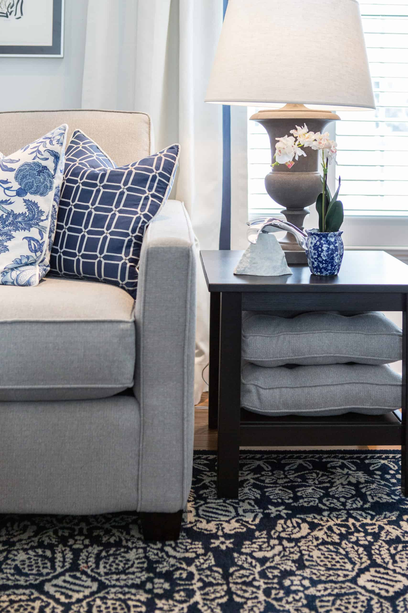 Blue pillows at the end of a white and gray couch