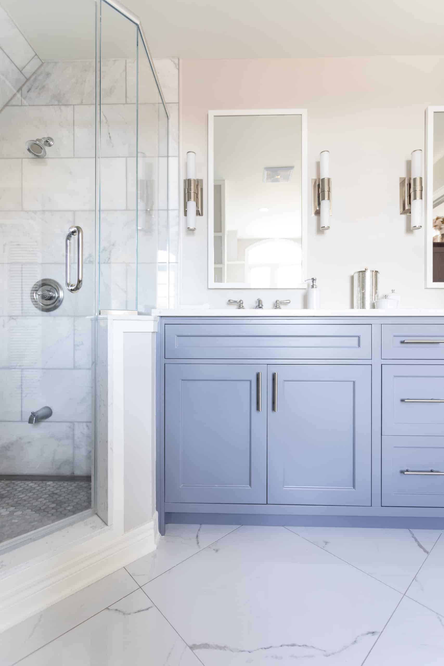 Blue double vanity next to a walk-in shower