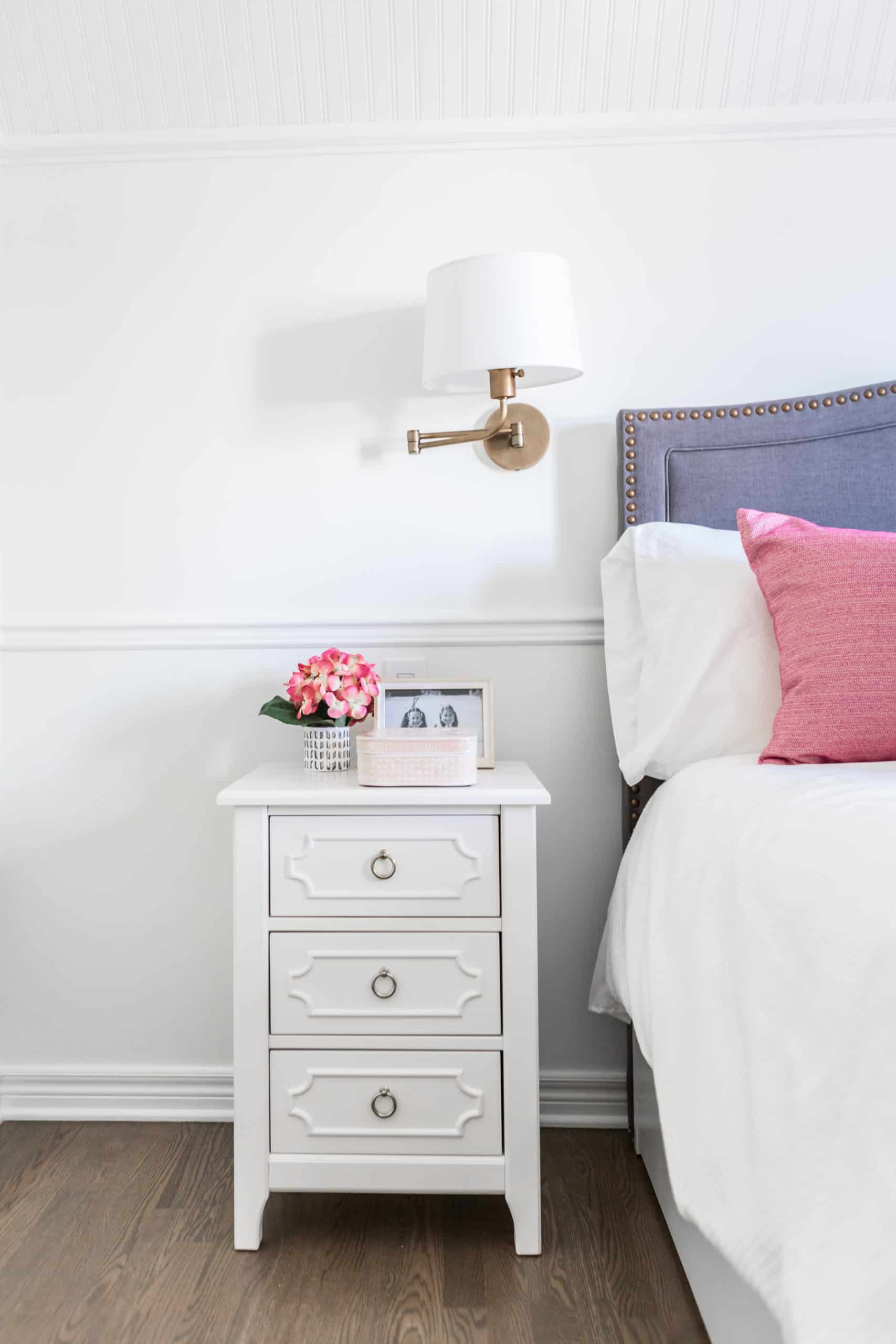 White, thin bedside table with flowers on it