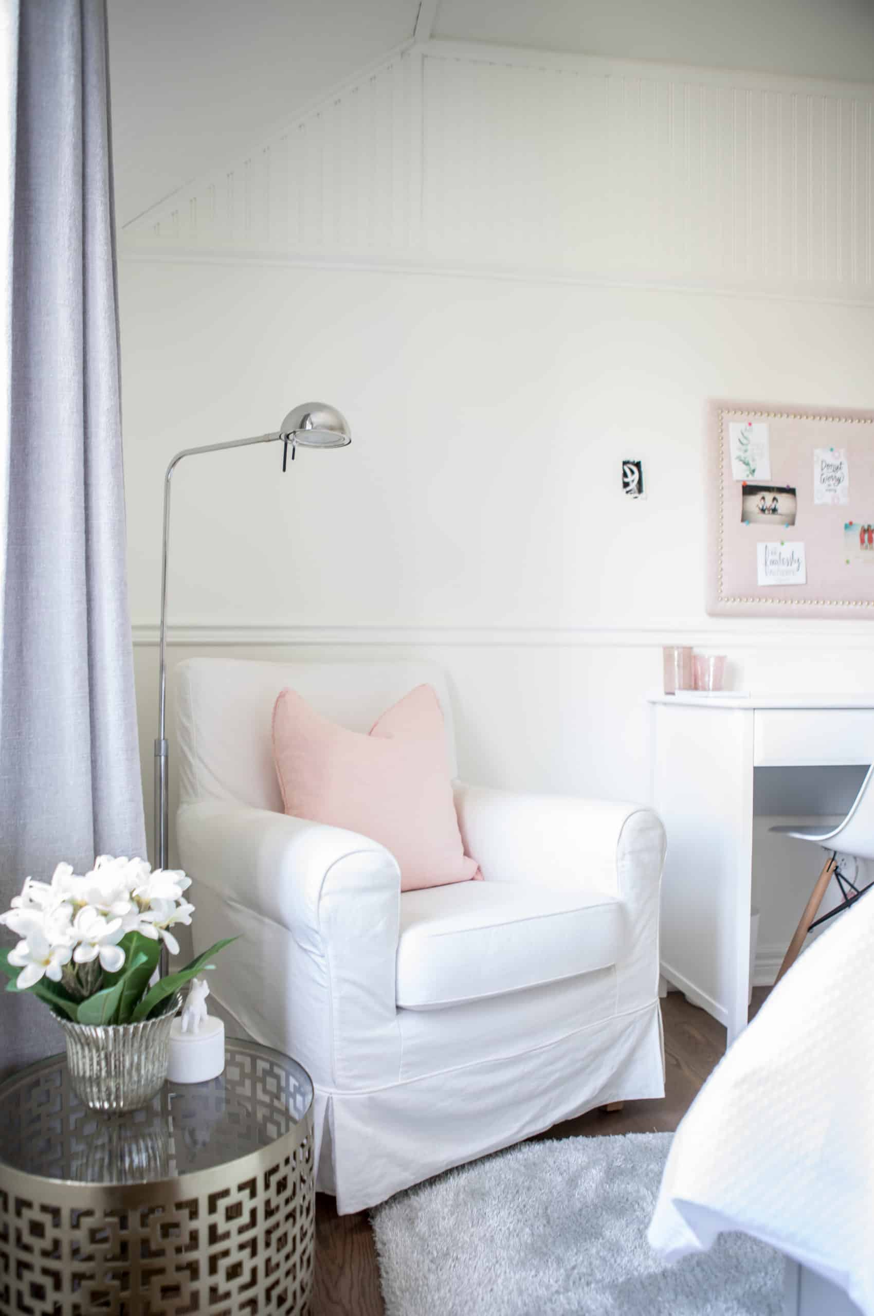 Bright white chair with a pink pillow on it